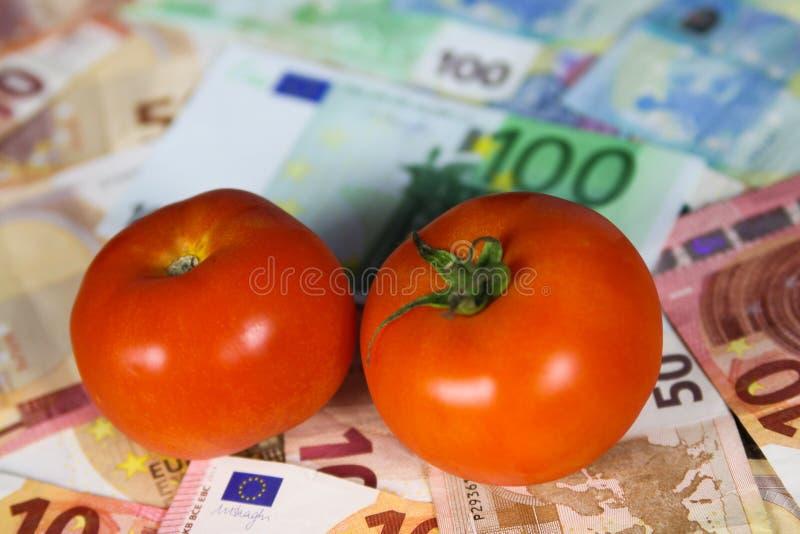 Conceito equilibrado saudável do custo da nutrição - dois tomates em euro- cédulas do papel moeda imagem de stock