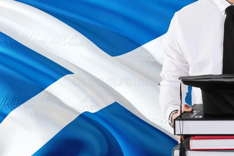 Conceito escocês bem sucedido da educação do estudante Guardando livros e tampão da graduação sobre o fundo da bandeira de Escóci foto de stock