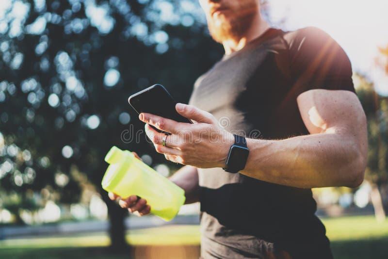 Conceito esperto da aptidão do exercício Atleta muscular novo que verifica o programm do treinamento na aplicação do smartphone a imagem de stock royalty free