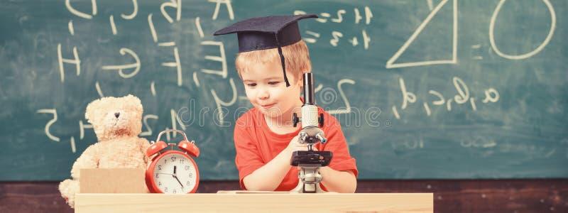 Conceito esperto da criança A criança na cara feliz guarda o microscópio Primeiro interessado anterior no estudo, aprendendo, edu fotos de stock royalty free