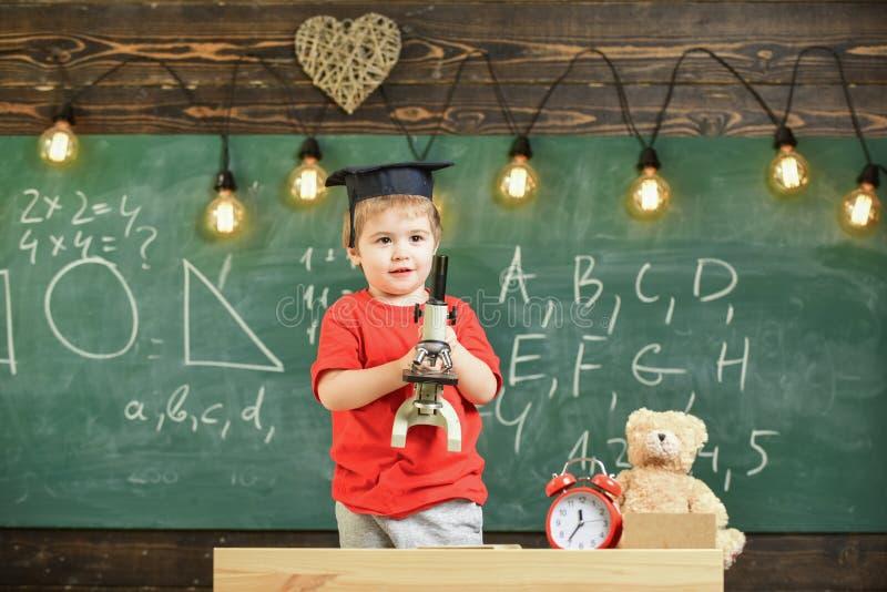 Conceito esperto da criança Primeiro interessado anterior no estudo, aprendendo, educação A criança na cara feliz guarda o micros imagens de stock