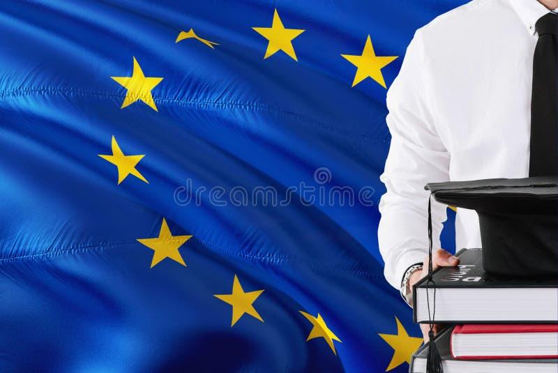 Conceito europeu bem sucedido da educação do estudante Guardando livros e tampão da graduação sobre o fundo da bandeira da União  foto de stock royalty free