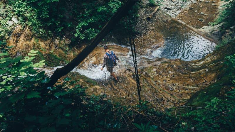 Conceito extremo dos esportes do exercício do apoio da cachoeira de Crosses Wild River do explorador do viajante do caminhante foto de stock