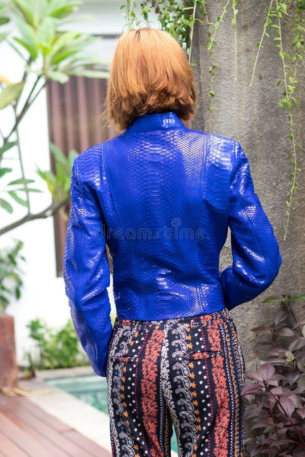 Conceito fêmea da beleza Retrato da moça elegante no levantamento luxuoso azul do revestimento e dos óculos de sol do pitão do sn imagens de stock