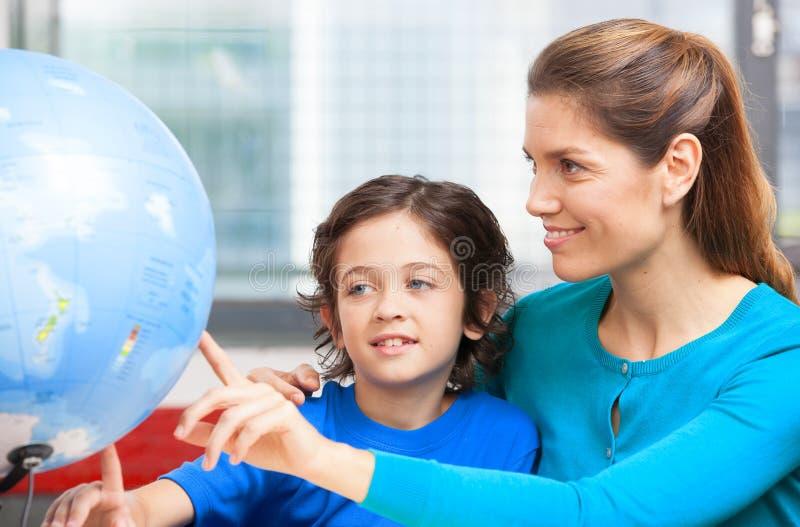 Conceito feliz da escola Professor fêmea que explica a geografia à criança foto de stock royalty free