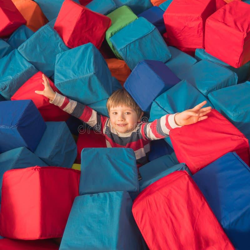 Conceito feliz da infância Menino que joga com blocos macios no centro de entretenimento Criança no bom humor que guarda as mãos  foto de stock royalty free