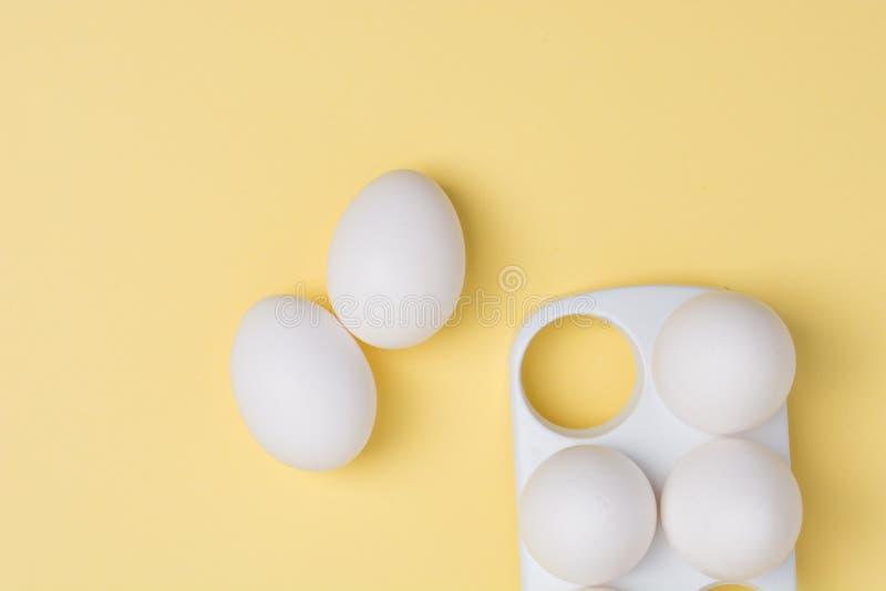 Conceito feliz de Easter Ovos brancos no fim amarelo do fundo acima fotografia de stock