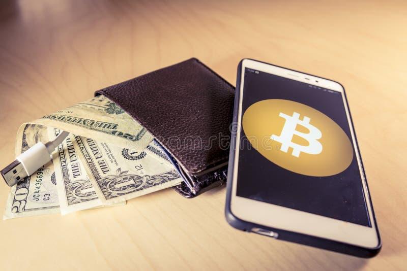 Conceito financeiro com uma carteira com dólares americanos, cabo de USB e smartphone com logotipo do bitcoin fotografia de stock royalty free