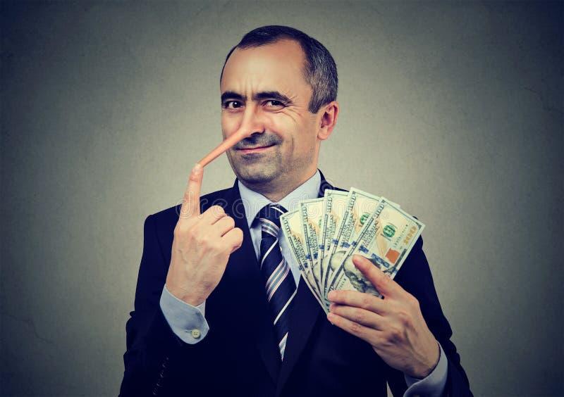 Conceito financeiro da fraude Executivo do homem de negócios do mentiroso com dinheiro do dólar fotografia de stock royalty free