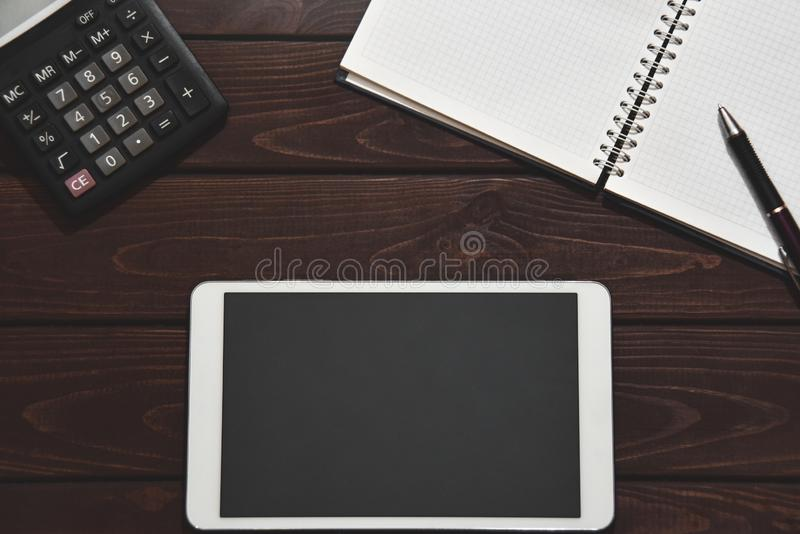 Conceito financeiro, PC da tabuleta, calculadora, bloco de notas no fundo de madeira, rendimento pessoal planejando r