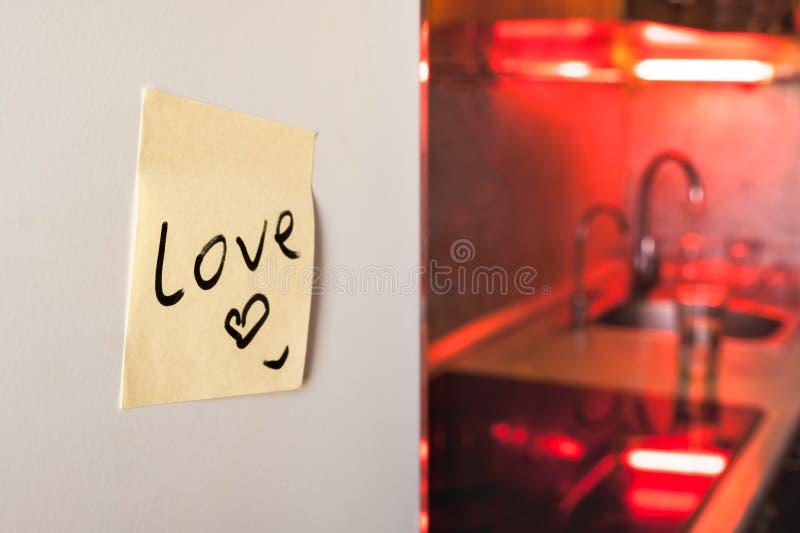 Conceito forte do relacionamento: uma nota do amor em um refrigerador com dispositivos de cozinha e luzes vermelhas no fundo borr fotografia de stock royalty free