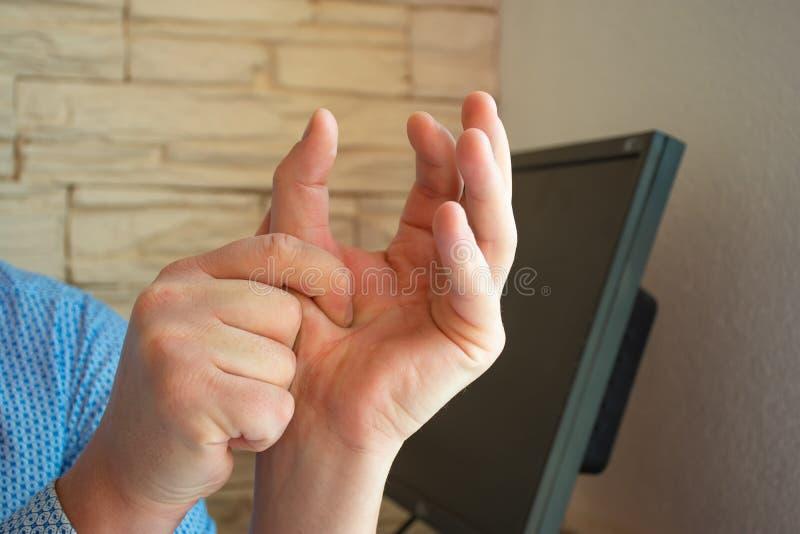 Conceito fotografia de dor ou espasmo no polegar O homem segura o polegar com a palma da outra mão, cujos músculos são espasmódic fotos de stock royalty free