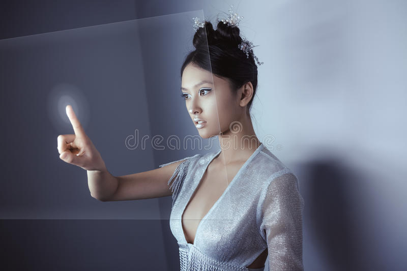 Conceito futuro Holograma digital tocante da mulher asiática bonita nova fotografia de stock