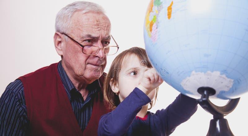 Conceito global do curso e da geografia Retrato do av? feliz e da neta que olham o globo e que planeiam o curso imagens de stock