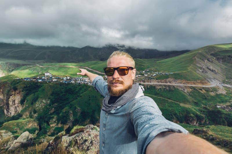 Conceito global do curso O homem novo do viajante com uma barba e os óculos de sol tomam um Selfie em um fundo de uma paisagem da imagens de stock