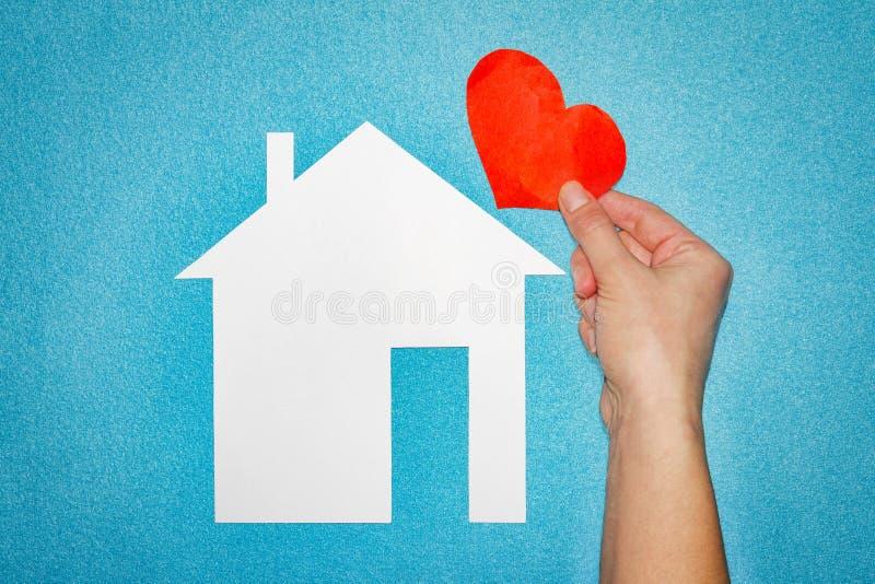 Conceito home do amor mão fêmea com coração vermelho sobre a casa do Livro Branco no fundo azul imagem de stock