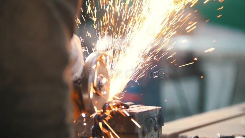 Conceito industrial Canteiro de obras A moedura do trabalhador do homem Sparkles do fogo foto de stock