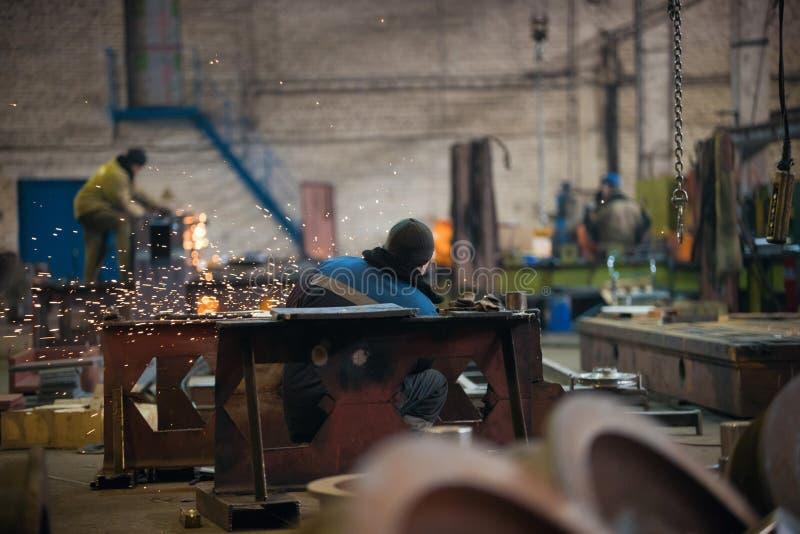 Conceito industrial Um homem que senta-se em seu local de trabalho e que usa o moedor Sparkles do fogo imagem de stock royalty free