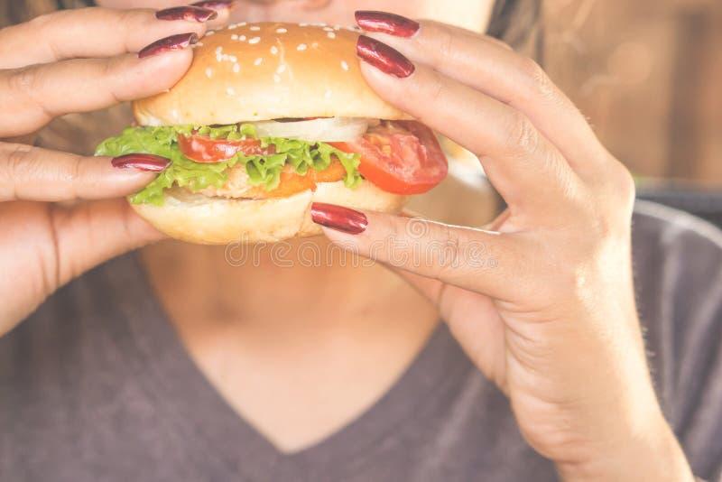 Conceito insalubre da comida lixo do close up do hamburguer comer da mão da mulher fotografia de stock royalty free