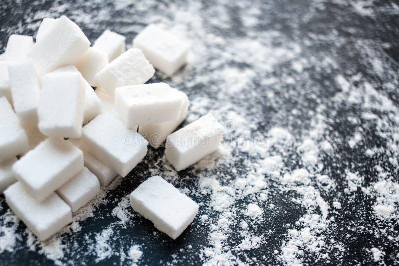 Conceito insalubre do alimento - açúcar e farinha em um fundo preto imagens de stock