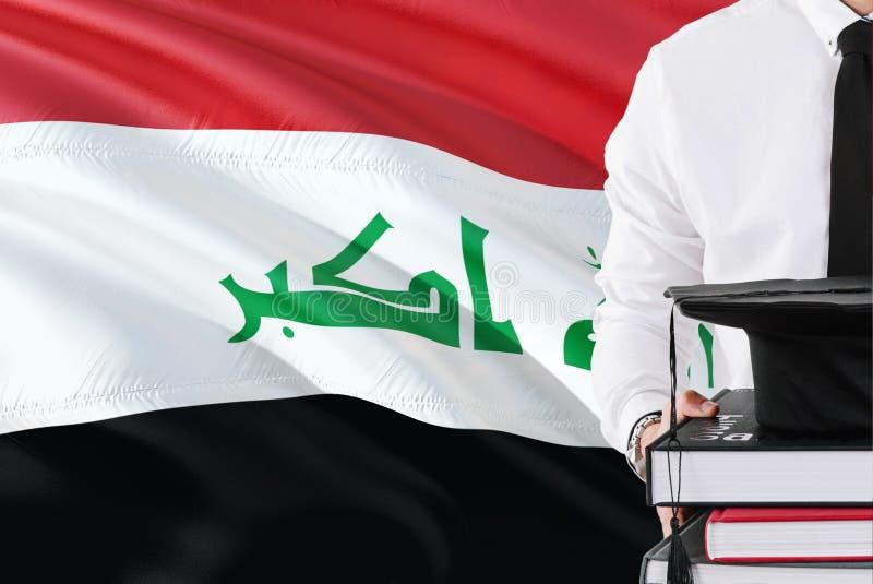 Conceito iraquiano bem sucedido da educação do estudante Guardando livros e tampão da graduação sobre o fundo da bandeira de Iraq foto de stock royalty free