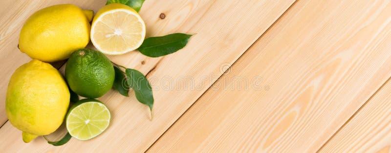 Conceito longo em um fundo de madeira, um grupo dos limões com galhos, lugar para uma inscrição imagem de stock