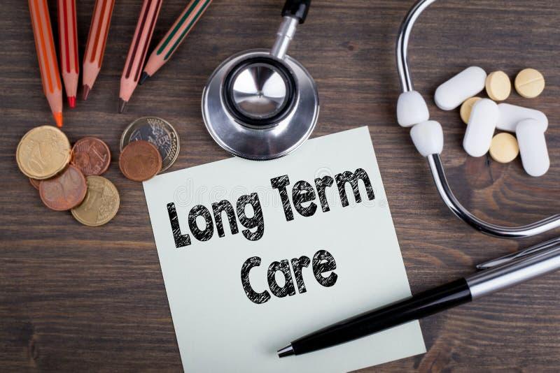 Conceito a longo prazo do cuidado Mesa com stetascope, dinheiro e tabuletas fundo para cuidados médicos fotografia de stock royalty free