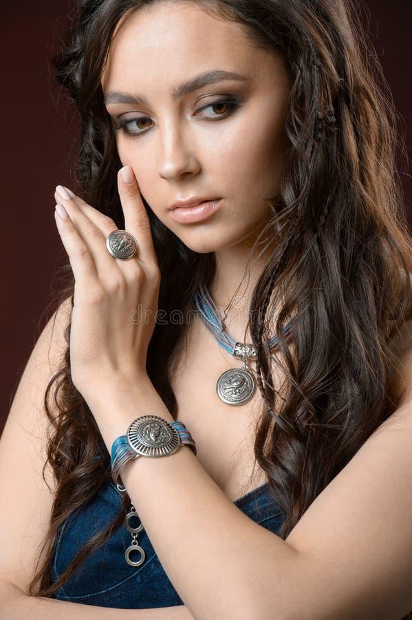 Conceito luxuoso da joia e da forma Um modelo com brincos colar e anel no fundo marrom fotos de stock