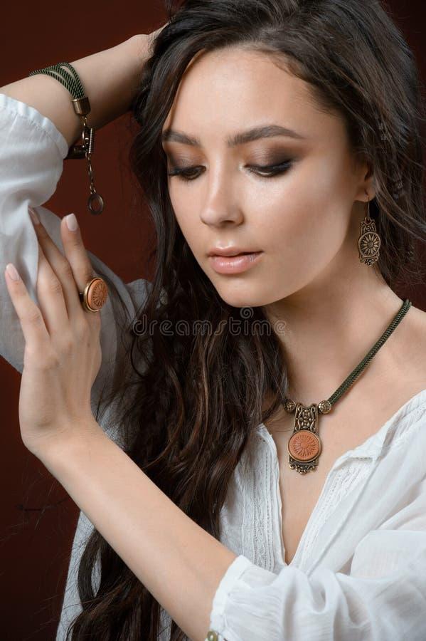 Conceito luxuoso da joia e da forma Um modelo com brincos colar e anel no fundo marrom imagem de stock royalty free