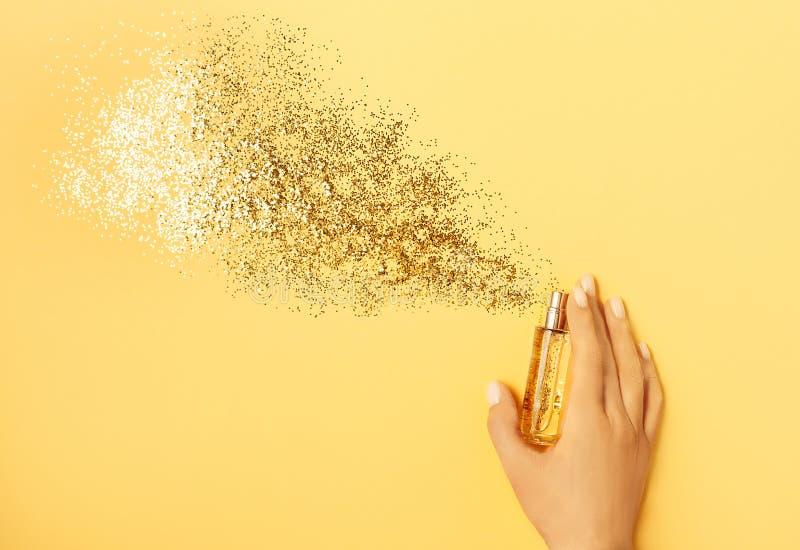 Conceito luxuoso do perfume Mão fêmea que guarda a garrafa à moda do perfume com pulverizador dos sparkles no fundo amarelo fotografia de stock