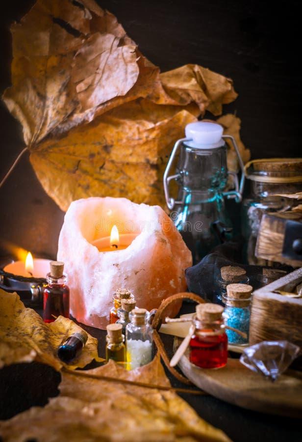Conceito mágico do outono Poções na garrafa e nas folhas fotos de stock royalty free