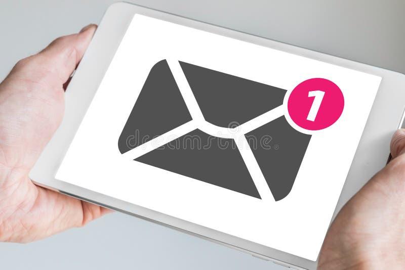 Conceito móvel do email e da mensagem indicado no écran sensível da tabuleta moderna realizado em duas mãos fotos de stock