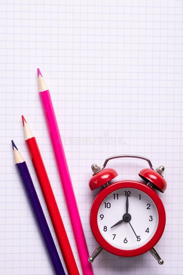 Conceito minimalistic do tempo da escola Lápis e cadernos coloridos e um despertador vermelho fotos de stock royalty free