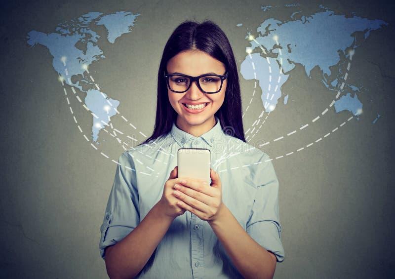 Conceito moderno da tecnologia de comunicação A mulher feliz com smartphone conectou o Internet da consultação no mundo inteiro imagem de stock royalty free