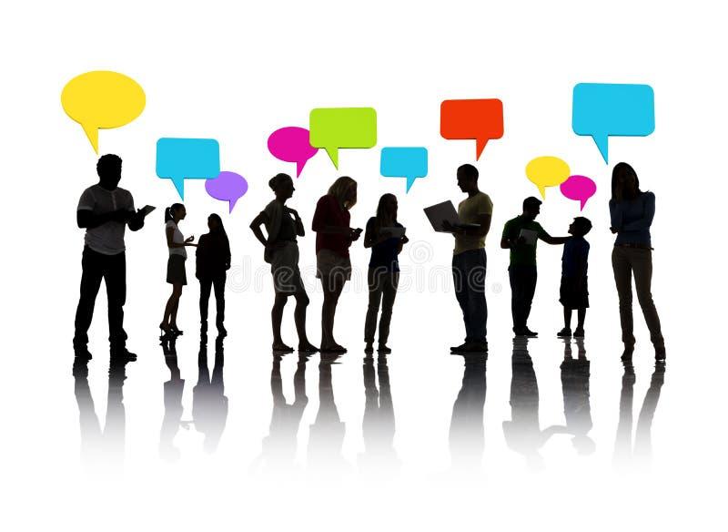 Conceito mostrado em silhueta das bolhas do discurso do grupo de pessoas fotos de stock