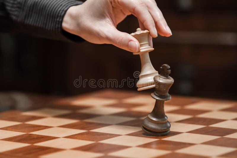 Conceito: a mulher que domina o homem A mão de uma mulher dá o checkmate ao rei com a rainha em um tabuleiro de xadrez de madeira fotografia de stock royalty free