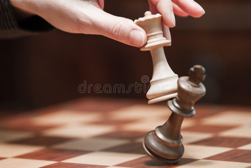 Conceito: a mulher que domina o homem A m?o de uma mulher d? o checkmate ao rei com a rainha em um tabuleiro de xadrez de madeira foto de stock