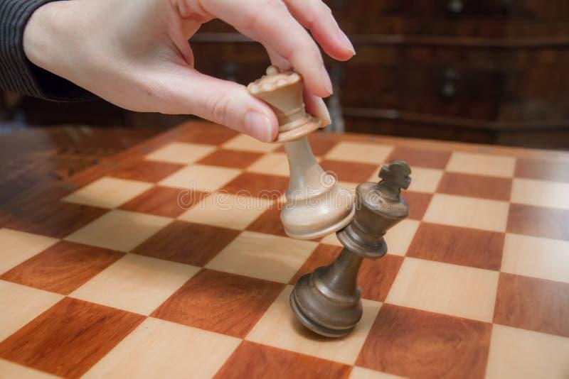 Conceito: a mulher que domina o homem A m?o de uma mulher d? o checkmate ao rei com a rainha em um tabuleiro de xadrez de madeira foto de stock royalty free