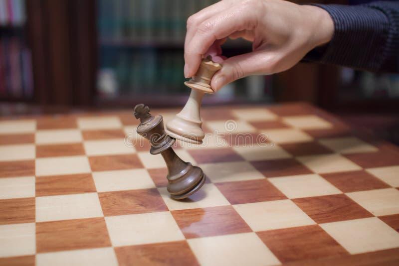 Conceito: a mulher que domina o homem A m?o de uma mulher d? o checkmate ao rei com a rainha em um tabuleiro de xadrez de madeira fotos de stock royalty free