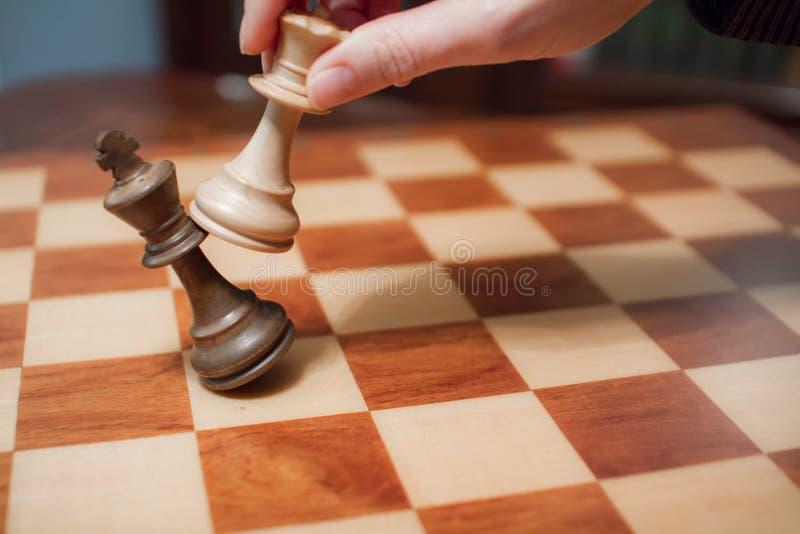 Conceito: a mulher que domina o homem A m?o de uma mulher d? o checkmate ao rei com a rainha em um tabuleiro de xadrez de madeira fotografia de stock royalty free