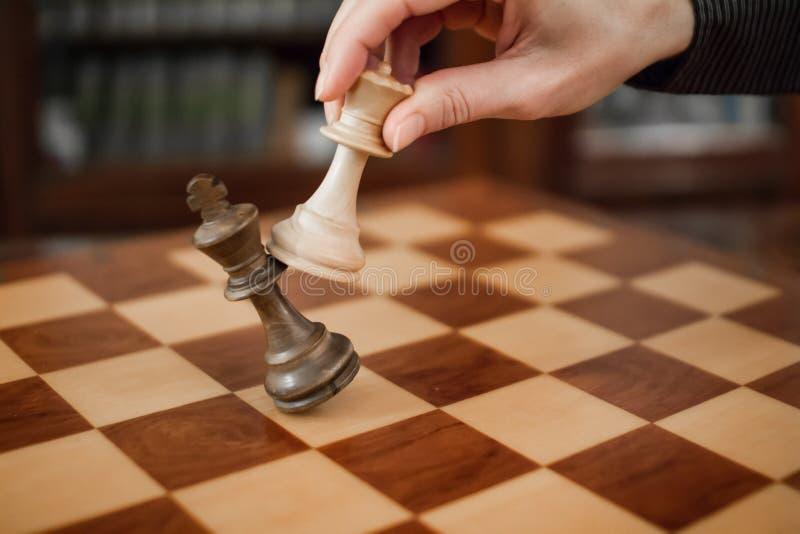 Conceito: a mulher que domina o homem A m?o de uma mulher d? o checkmate ao rei com a rainha em um tabuleiro de xadrez de madeira imagem de stock royalty free