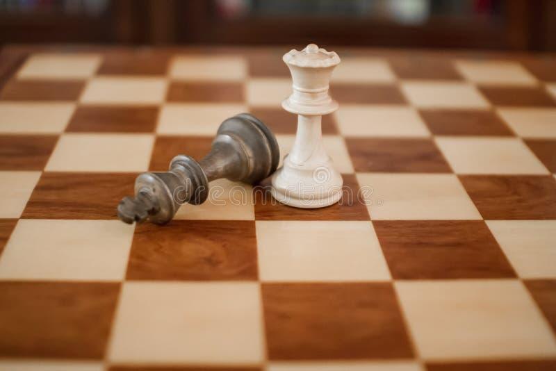 Conceito: a mulher que domina o homem Uma placa de xadrez de madeira com o rei na terra após o checkmate e a rainha foto de stock royalty free