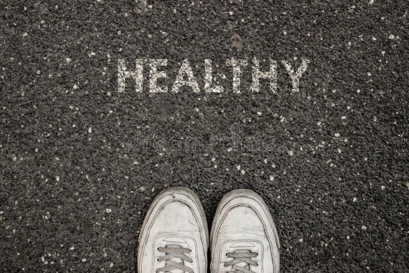 Conceito novo da vida, sapatas do esporte e a palavra SAUDÁVEL! escrito na terra do asfalto, slogan inspirador imagens de stock