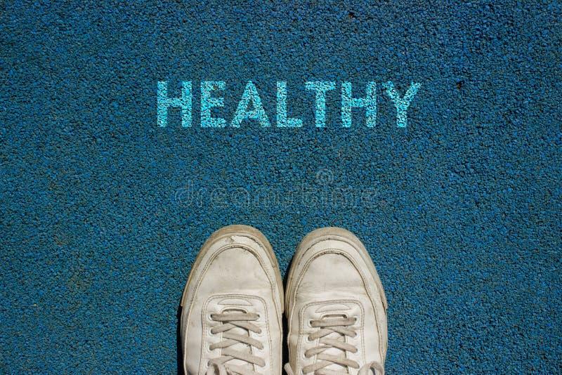 Conceito novo da vida, sapatas do esporte e a palavra SAUDÁVEL! escrito na terra azul da passagem, slogan inspirador imagem de stock royalty free