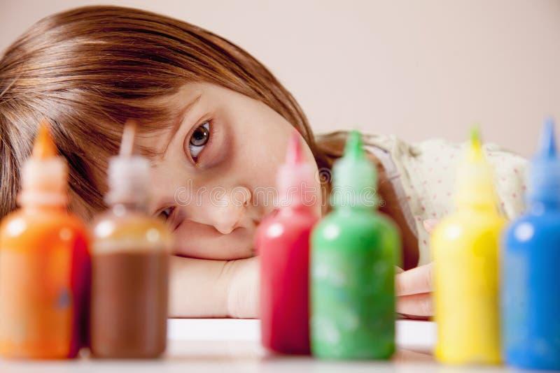 Conceito: o mundo é colorfu Pouco menina bonito que olha para fora para pinturas coloridas imagem de stock royalty free