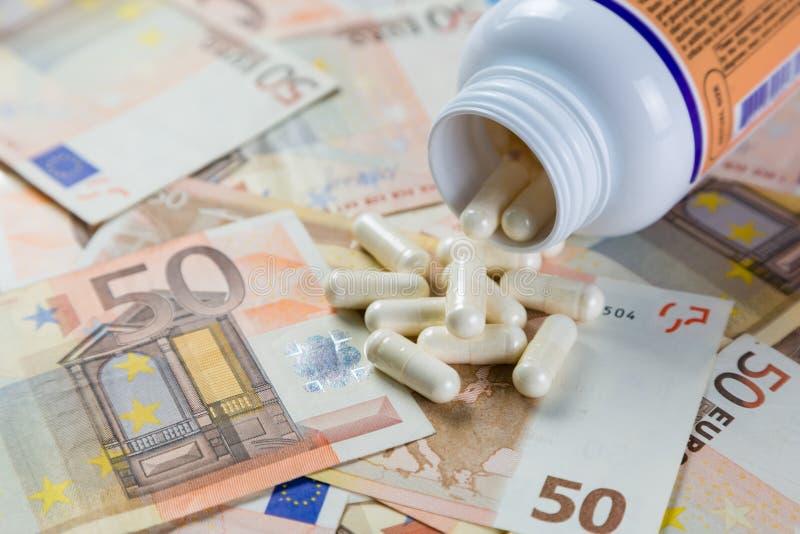 Conceito Overpriced das drogas - comprimidos do recipiente em contas do monet fotografia de stock royalty free