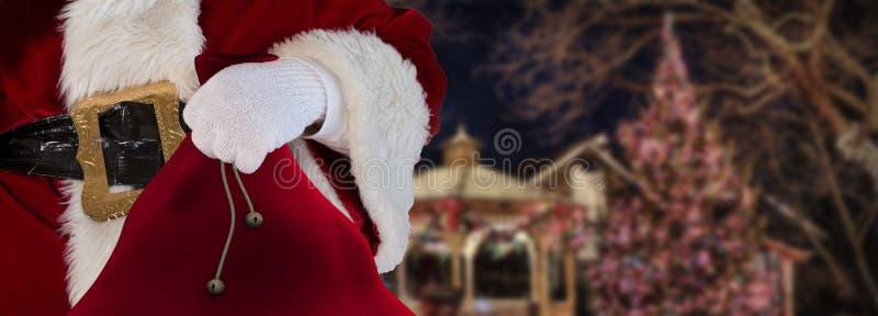 Conceito Papai Noel do Natal que está em uma cidade decorada que mantém o seu saco completo dos presentes imagens de stock