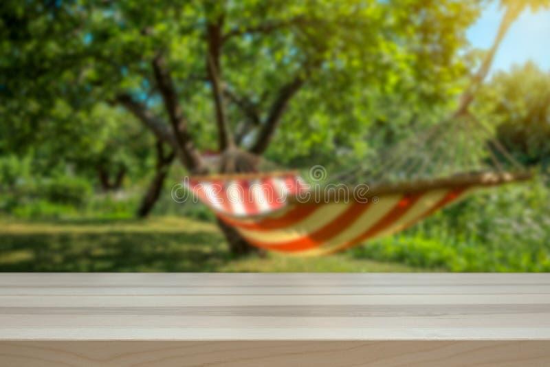 Conceito para o feriado e dias preguiçosos Rede em um jardim verde ensolarado borrado no foto de stock royalty free