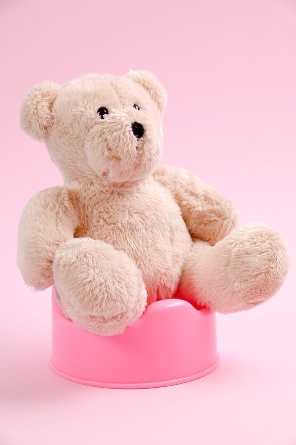 Conceito para o trem do urinol Um urso de peluche que senta-se em um potenciômetro imagens de stock