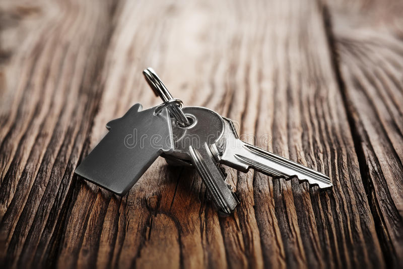 Conceito, porta-chaves e chaves dos bens imobiliários no fundo de madeira imagens de stock royalty free